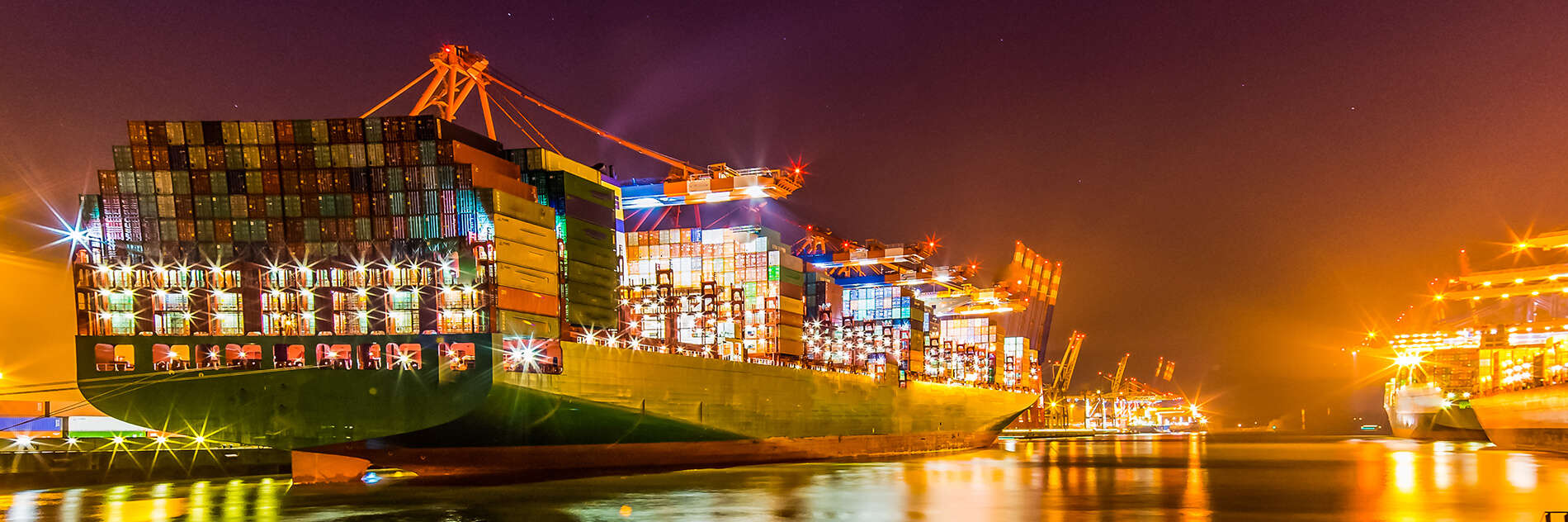 A huge international cargo ship anchored at port during a night time loading session
