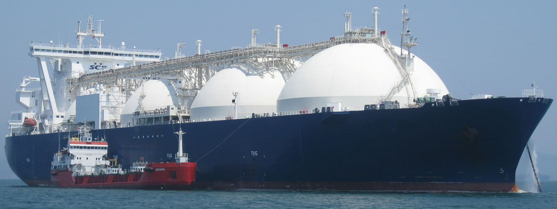 Another large Liquid Natural Gas (LNG) Carrier with adjacent red tug and a ship loan